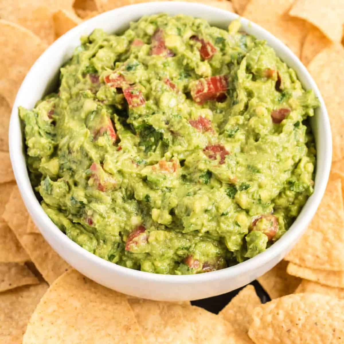 guacamole with tomatoes in a serving bowl surrounded by tortilla chips