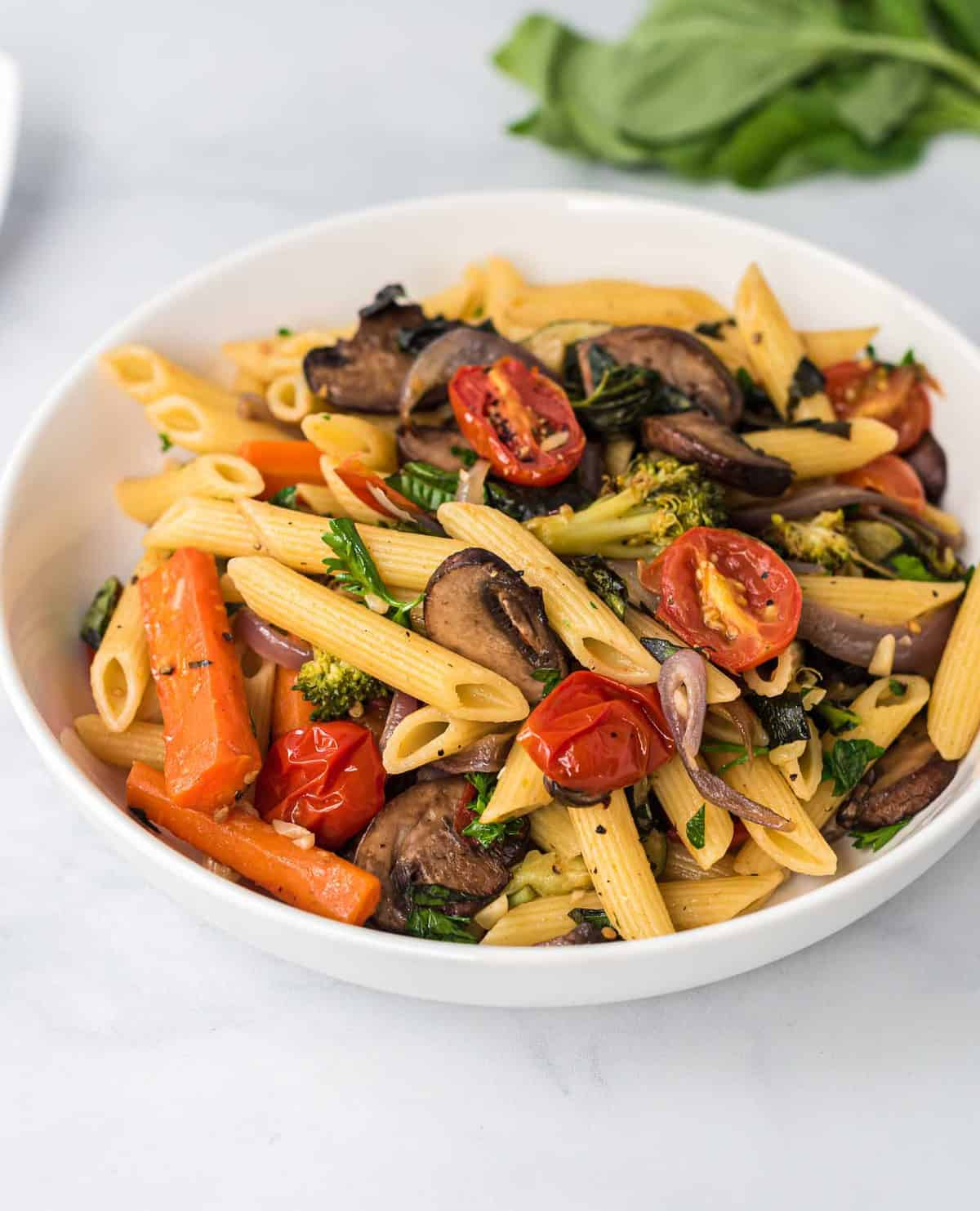 roasted vegetable pasta in a white bowl
