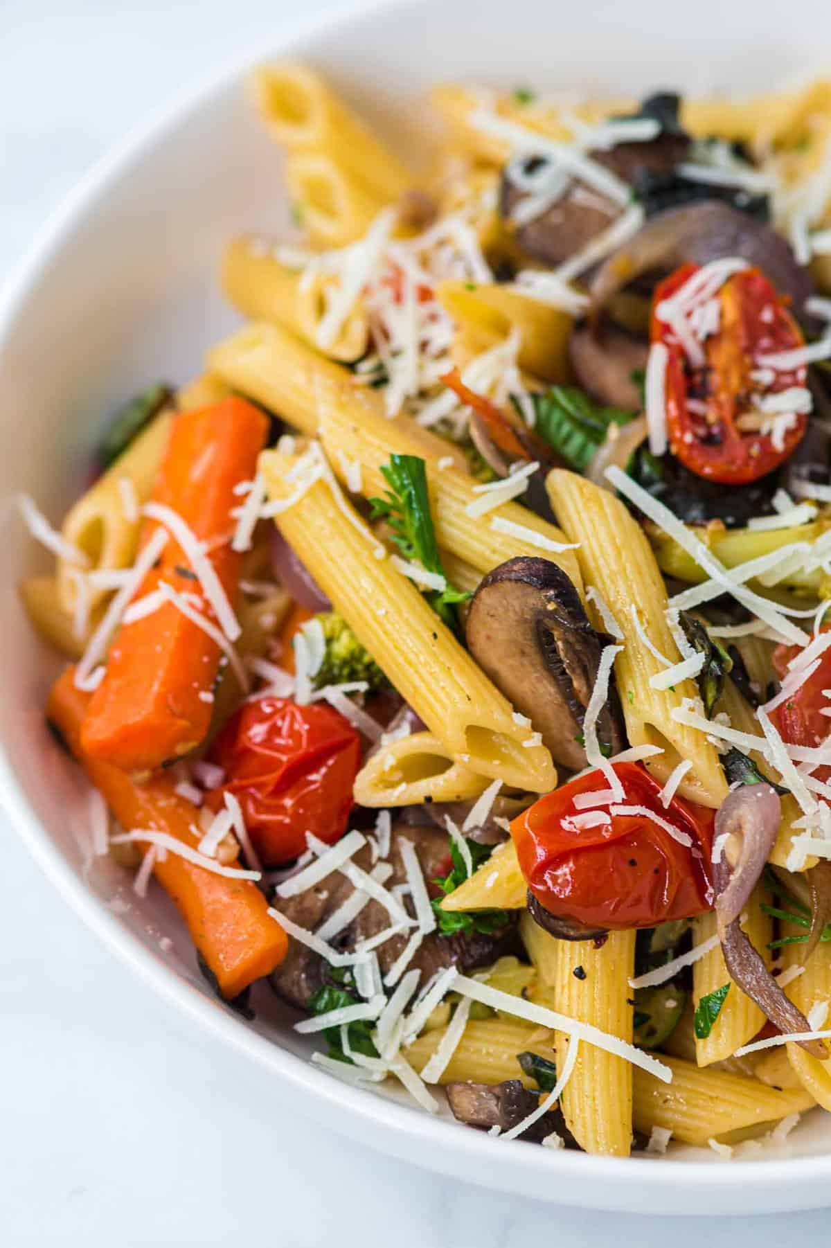 roasted vegetable pasta in a white bowl topped with parmesan cheese