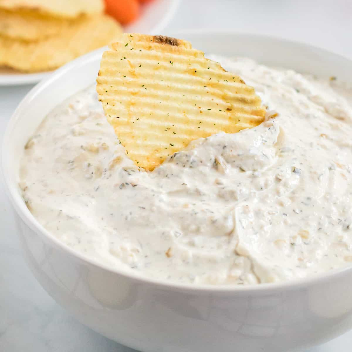 chip being dipped into sour cream chip dip