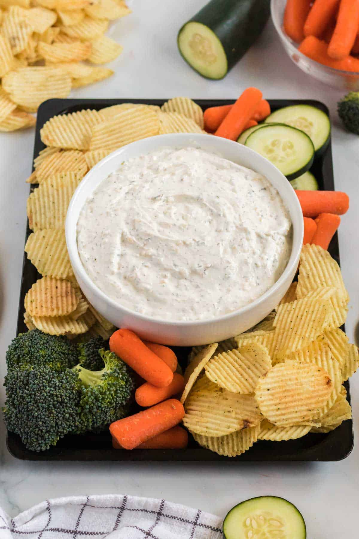 dip in a bowl surrounded by chips, broccoli, baby carrots, and cucumber