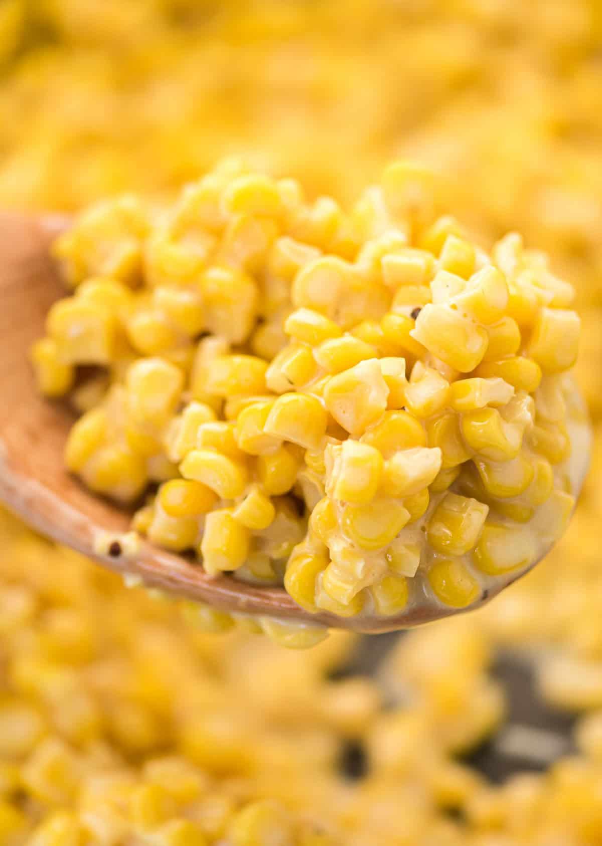 creamy corn on a wooden spoon