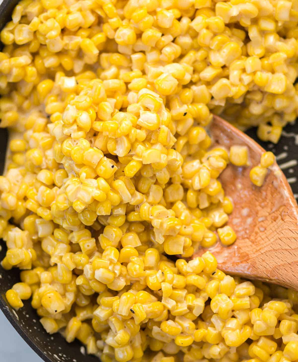 cream cheese honey corn in a skillet with a wooden spoon