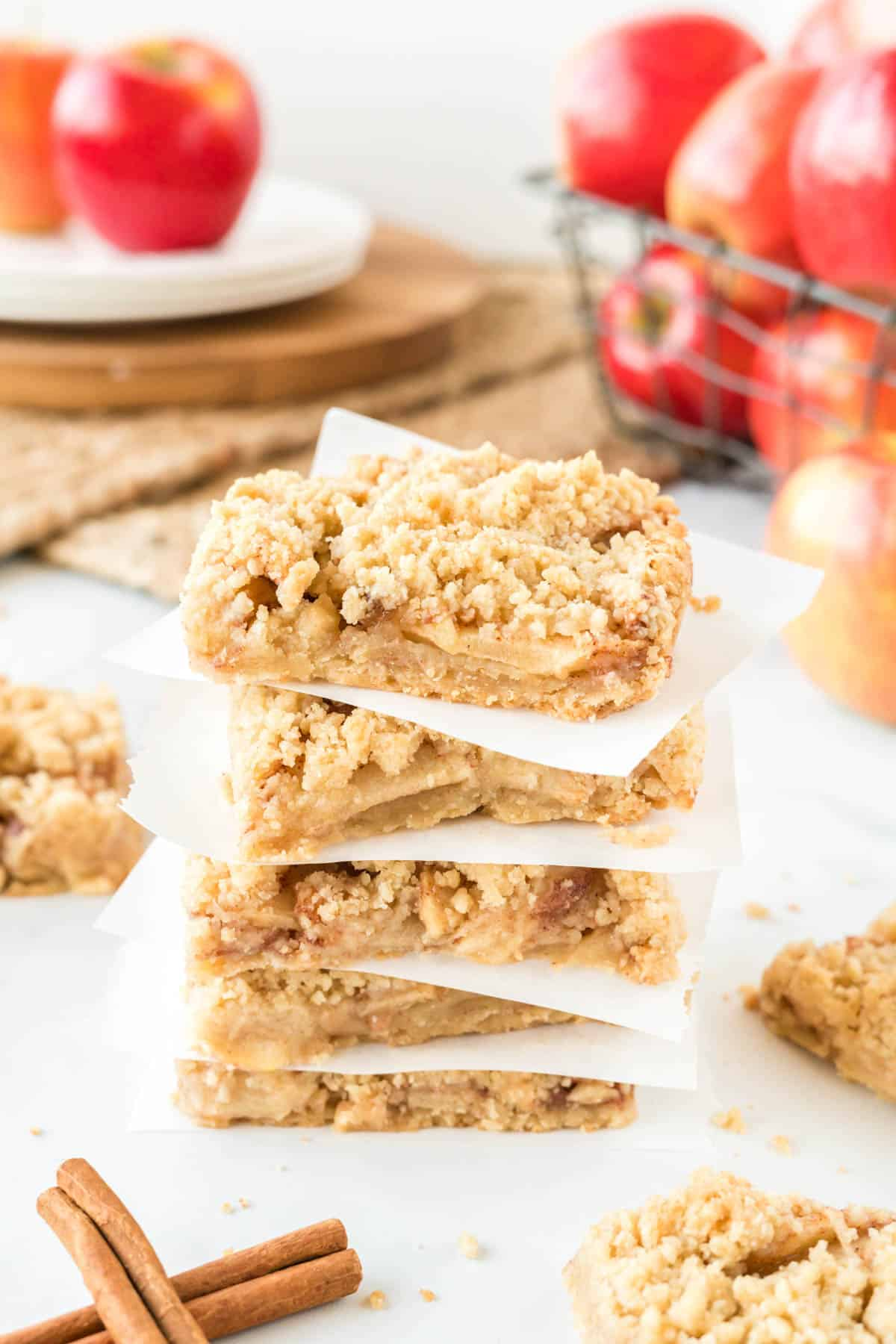 apple crisp bars stacked between squares of parchment paper