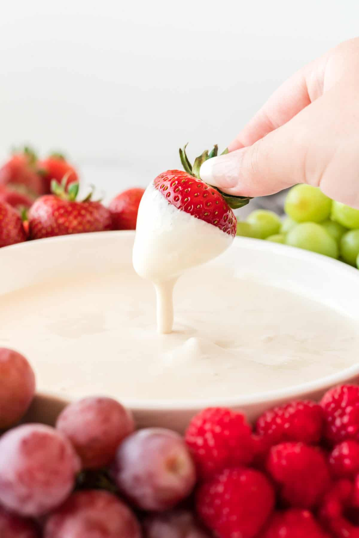 a strawberry being dipped into cream cheese yogurt dip
