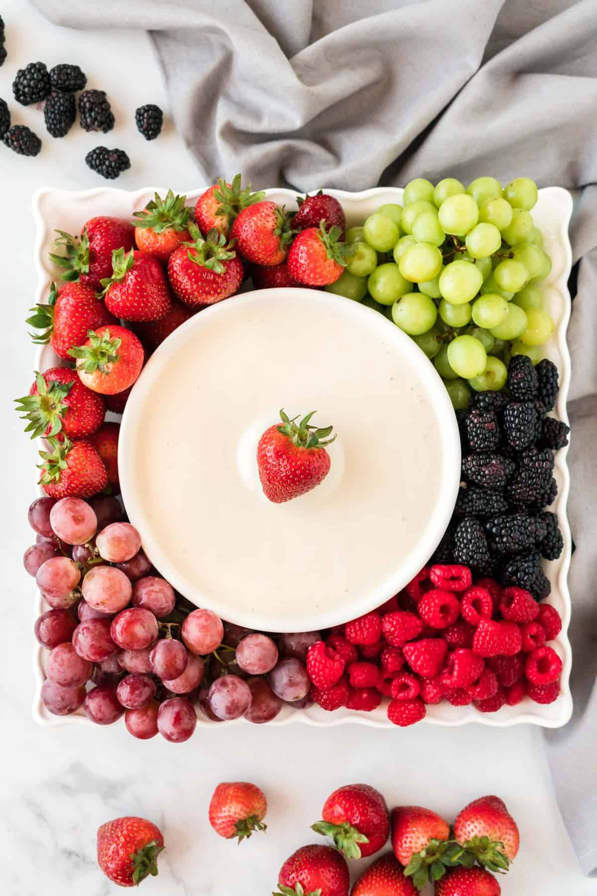 cream cheese dip in a bowl surrounded by fresh fruit on a platter
