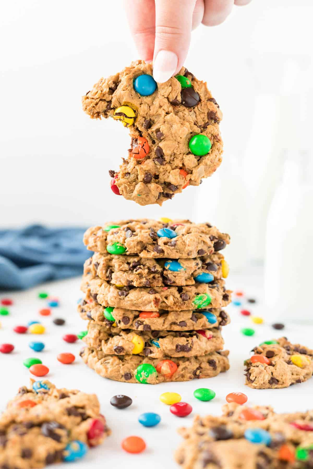 a hand taking a monster cookie with a bite out of it from a stack of cookies