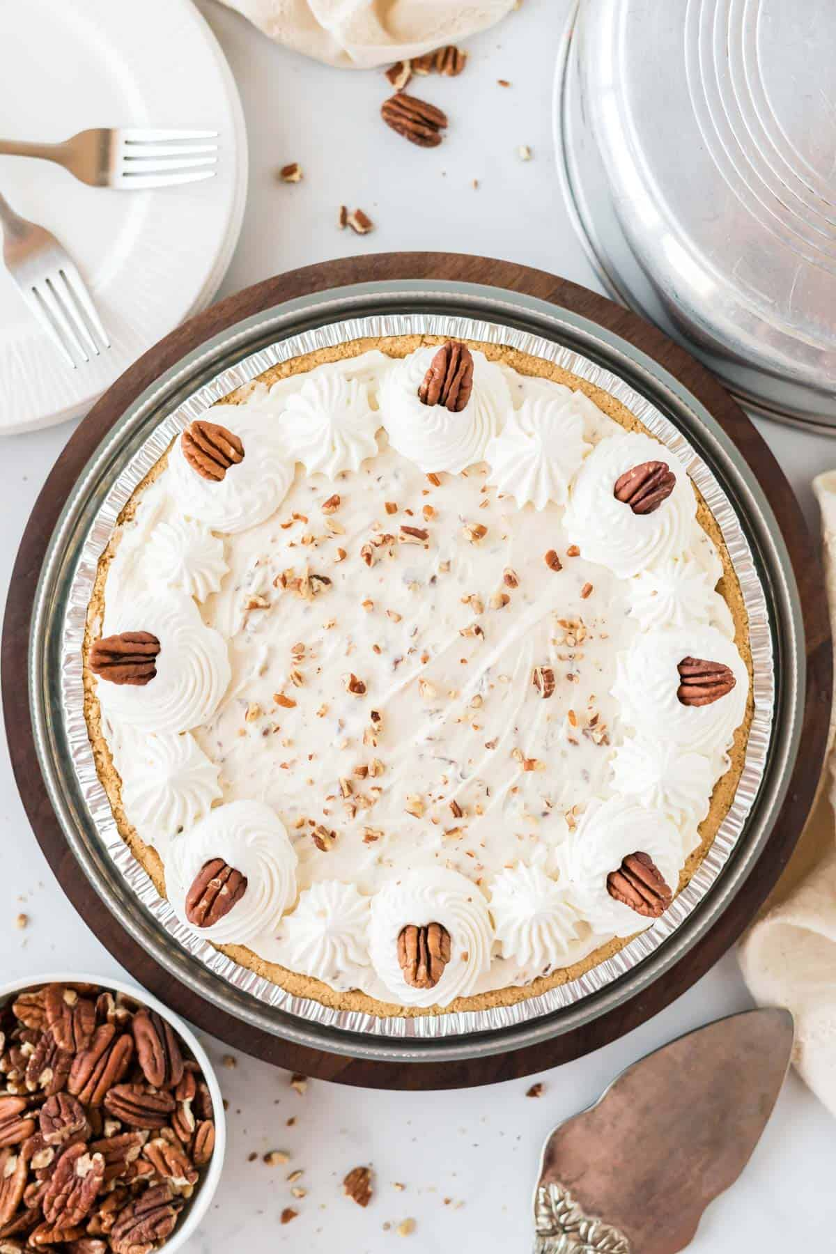 pecan cream pie decorated with whipped cream and pecans