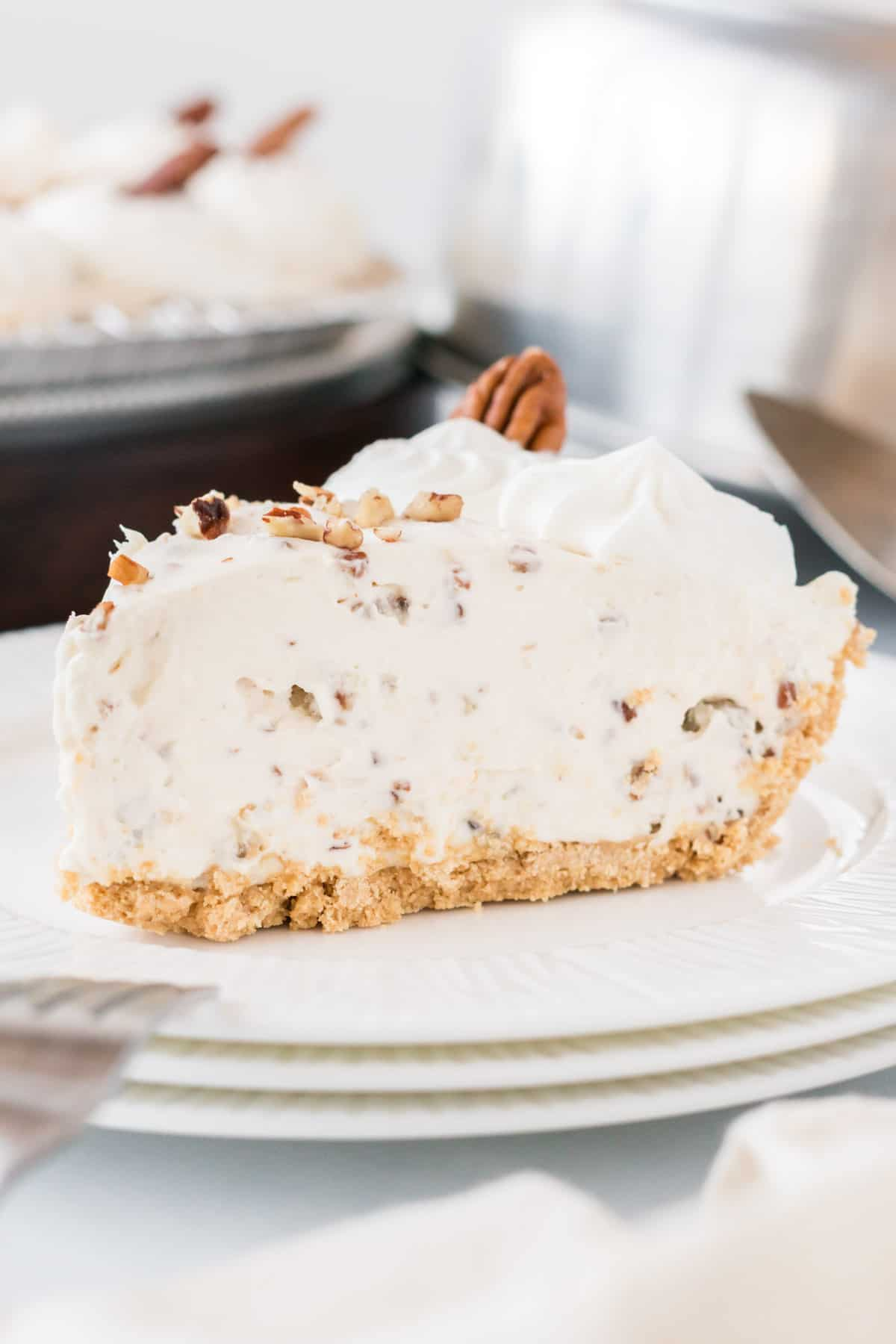 a slice of pecan cream pie on a white plate