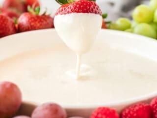 strawberry being dipped into cream cheese yogurt dip