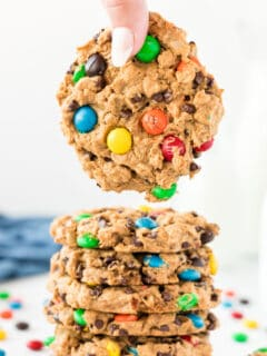 a hand taking a monster cookie from a stack of cookies