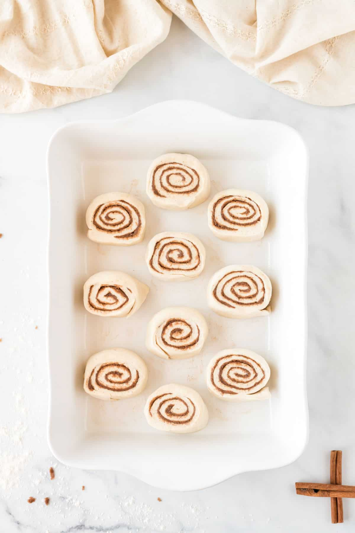 cinnamon roll dough slices in the baking dish
