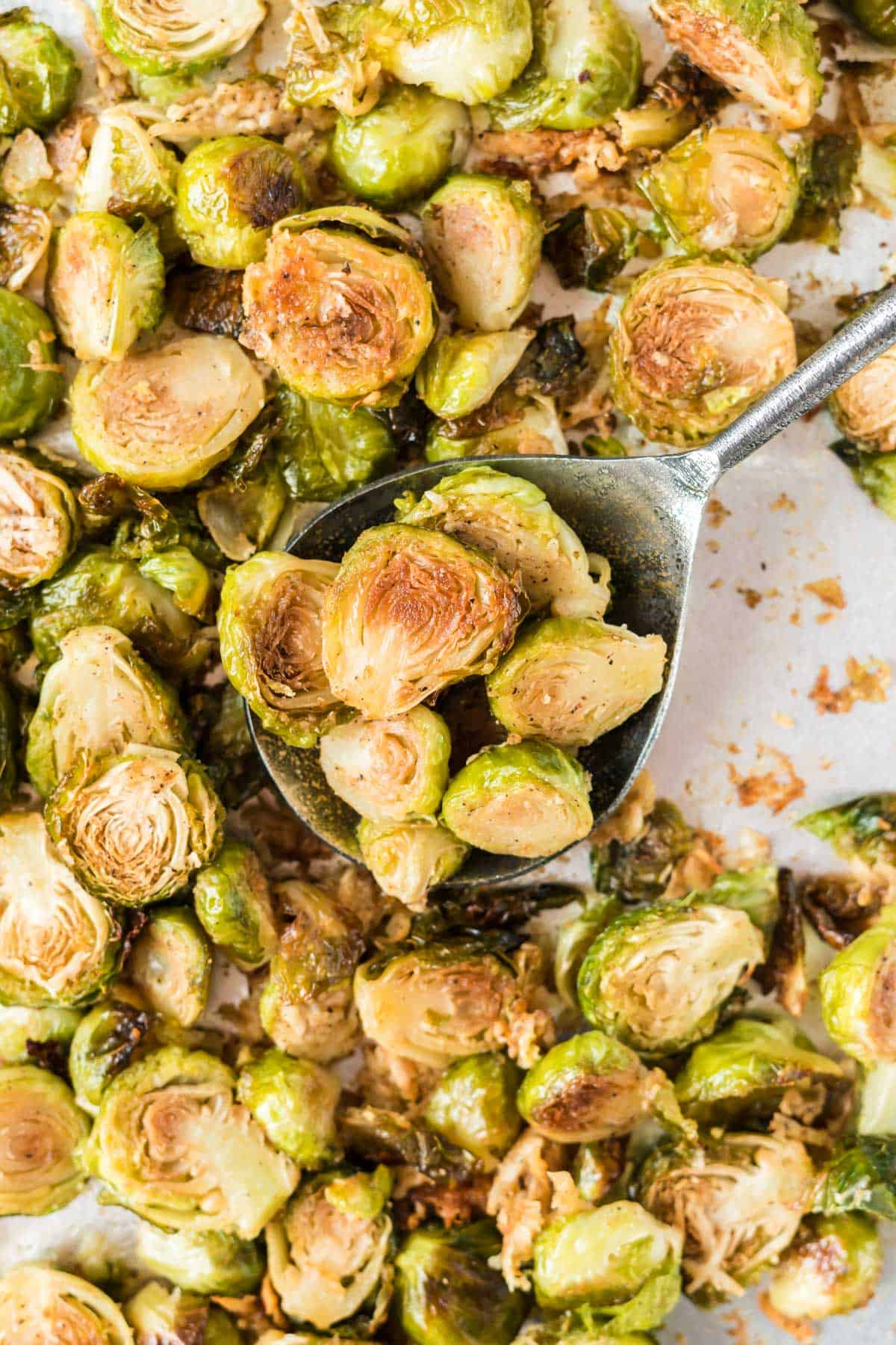 serving spoon taking a scoop of roasted brussel sprouts with parmesan from the baking sheet