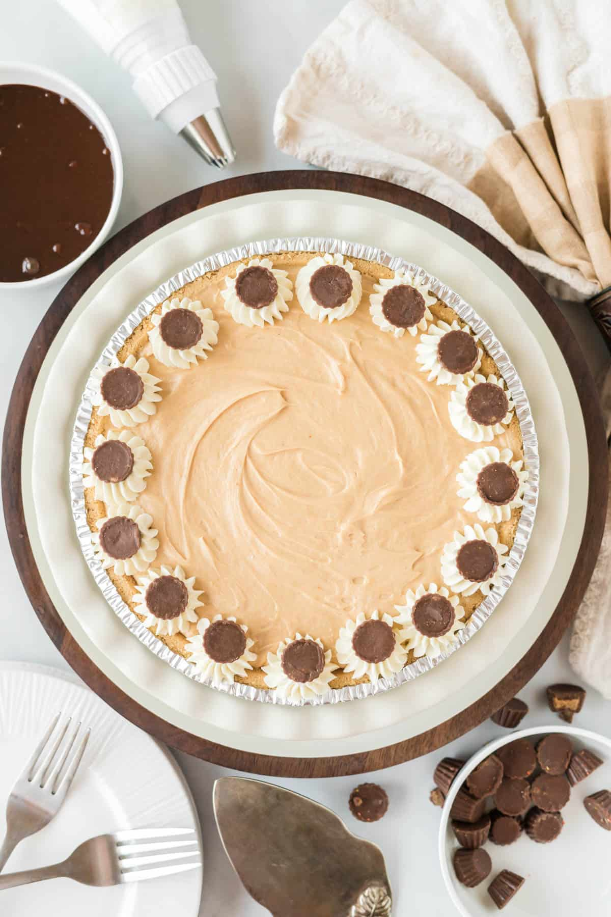 no bake peanut butter pie decorated with whipped cream and mini reese's cups
