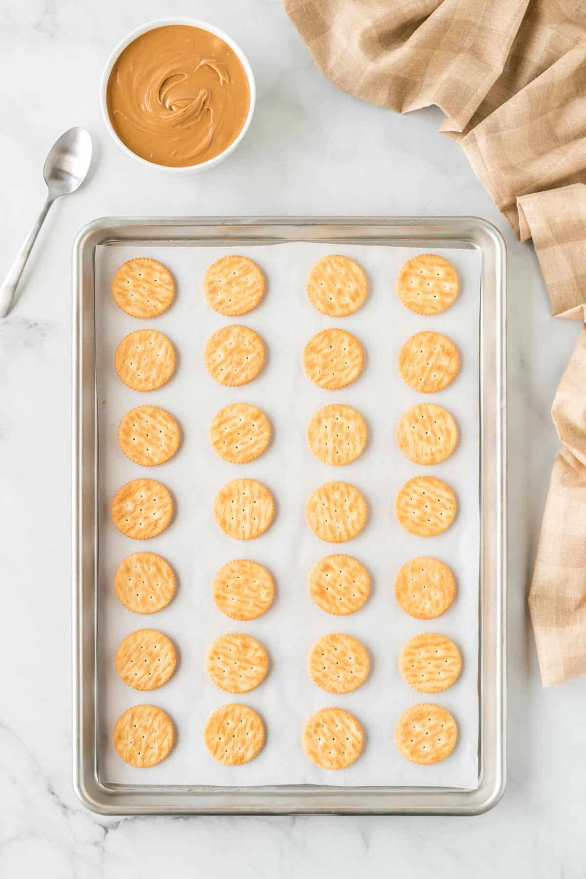 ritz crackers lined up on a baking sheet