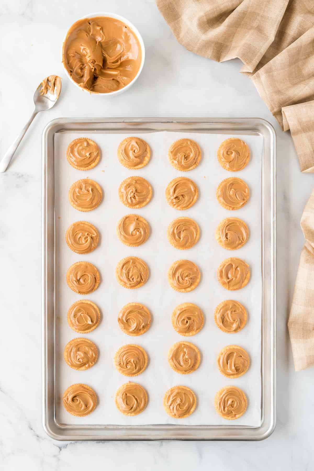 ritz crackers on a baking sheet topped with peanut butter
