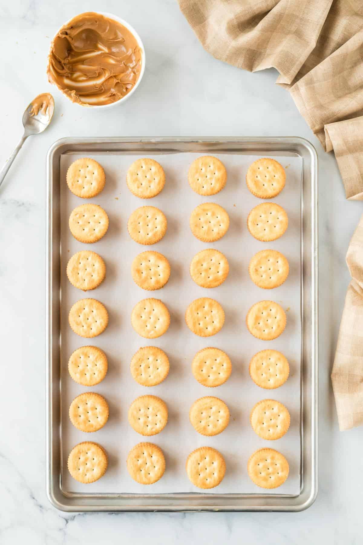 ritz cracker peanut butter sandwiches lined up on the baking sheet
