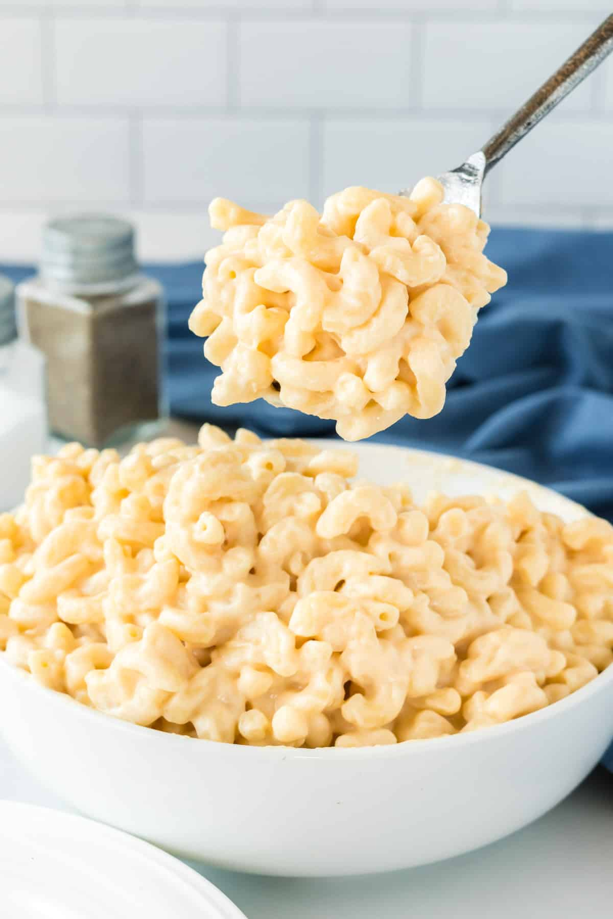 a spoon taking a scoop of mac and cheese from a bowl