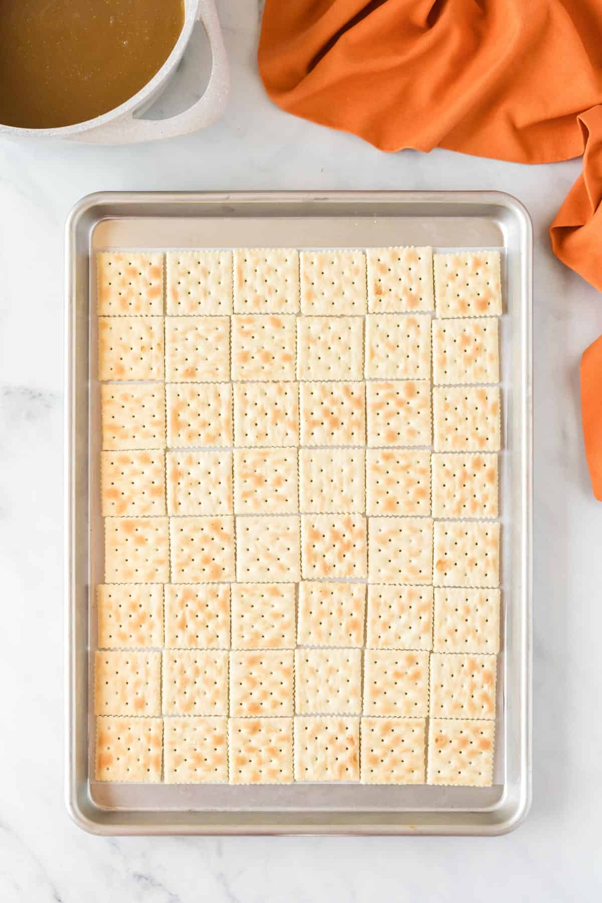 baking sheet lined with saltine crackers
