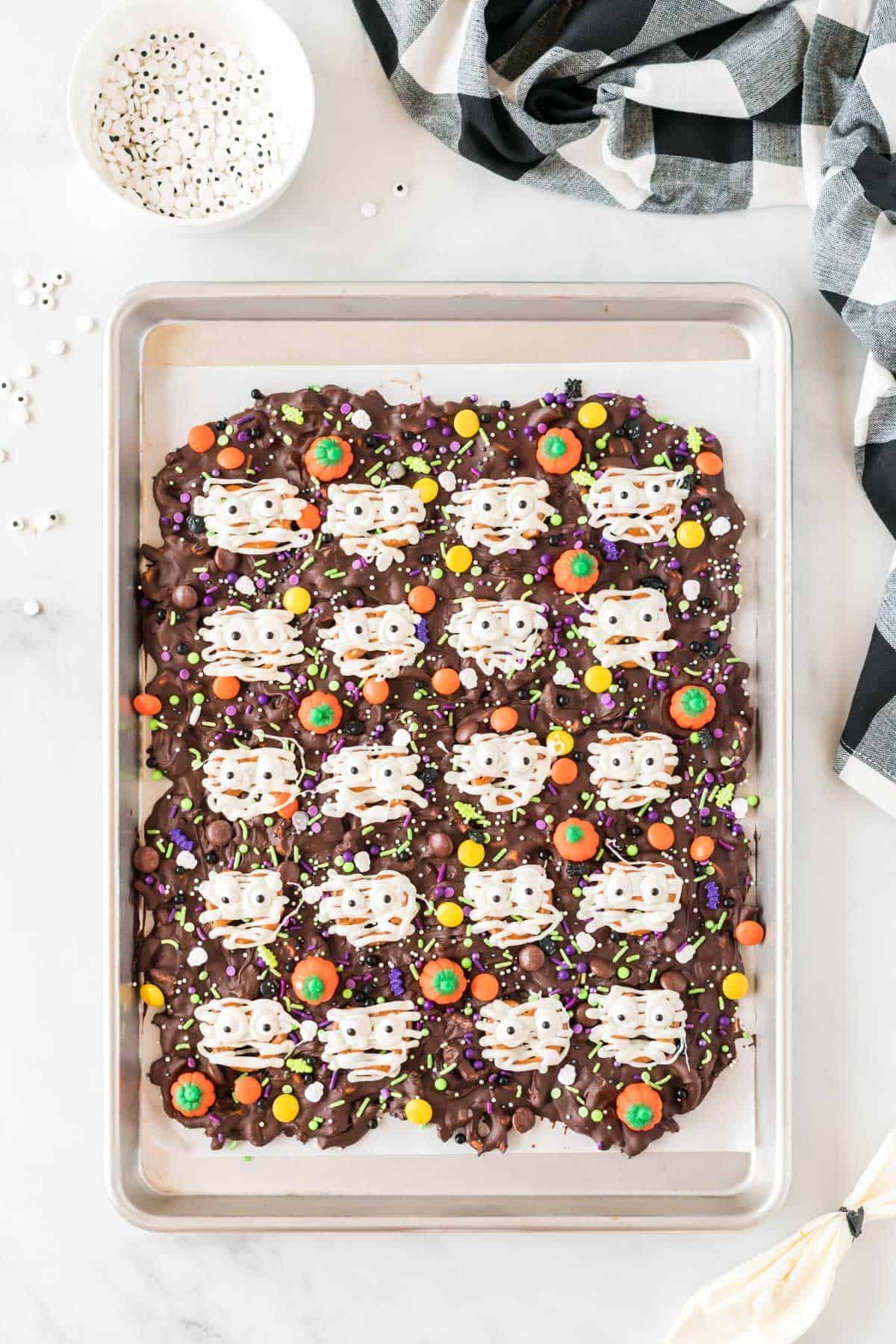 halloween bark with white chocolate drizzled over the pretzels