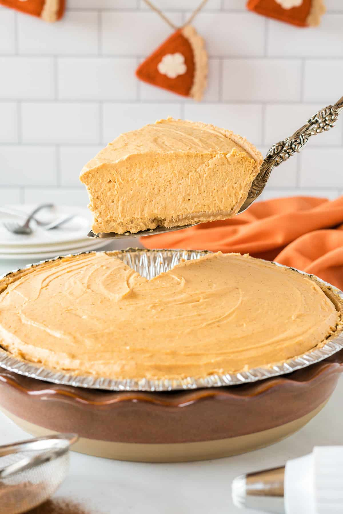 taking a piece of pumpkin pie from the pie dish
