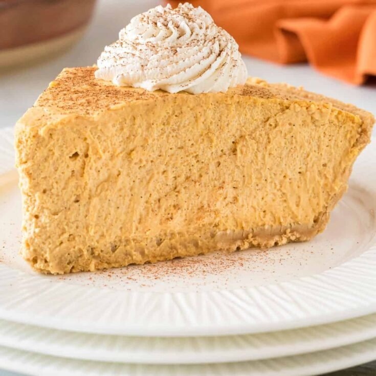 no bake pumpkin pie slice on a plate topped with whipped cream