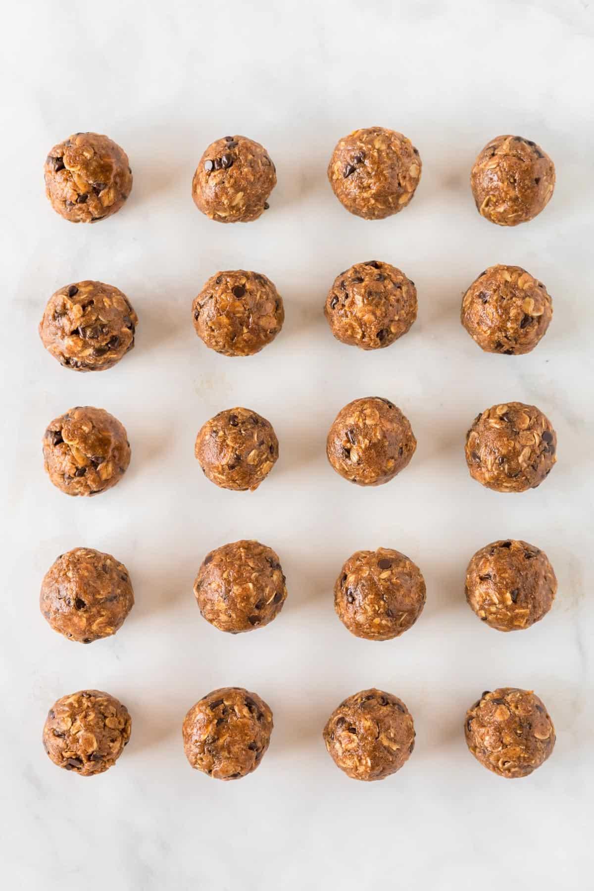 pumpkin protein balls lined up on a baking sheet