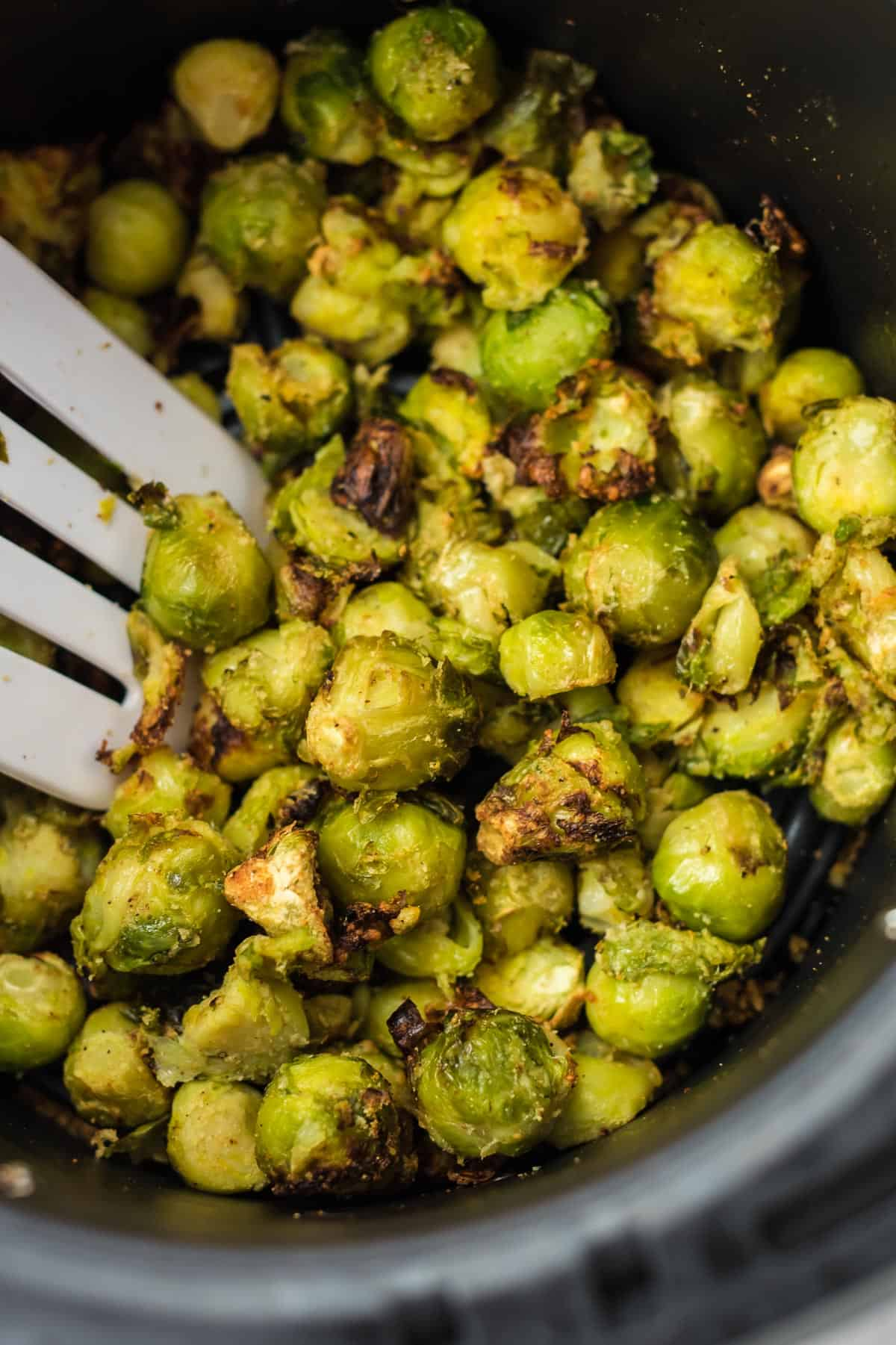 spatula taking a scoop of brussel sprouts from the air fryer